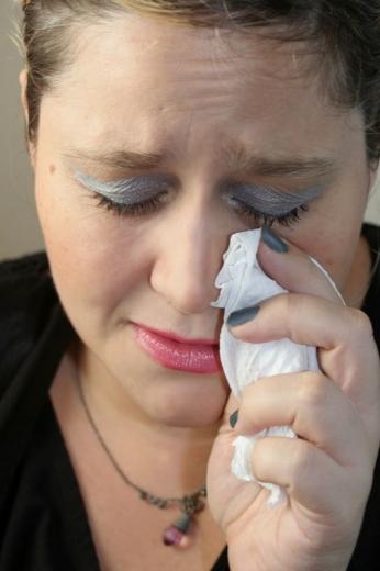 Egy nő szemét lecsukva, zsebkendővel törli a szemét.