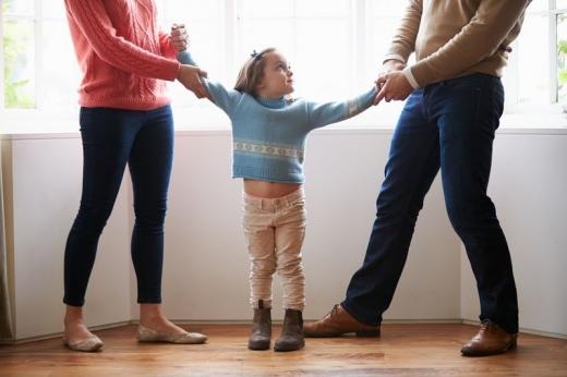 Egy férfi és egy nő között egy kislányt, amit mindketten maguk felé húznak.