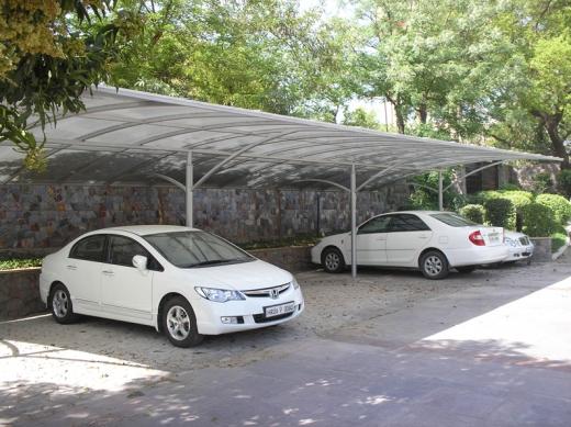Egy utcai fedett parkolóban áll 3 fehér autó.