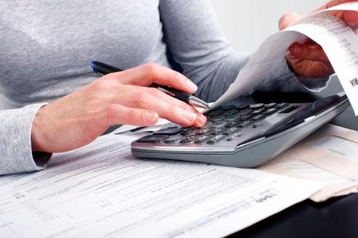 Egy kéz számológépen számolja a kiadásokat.