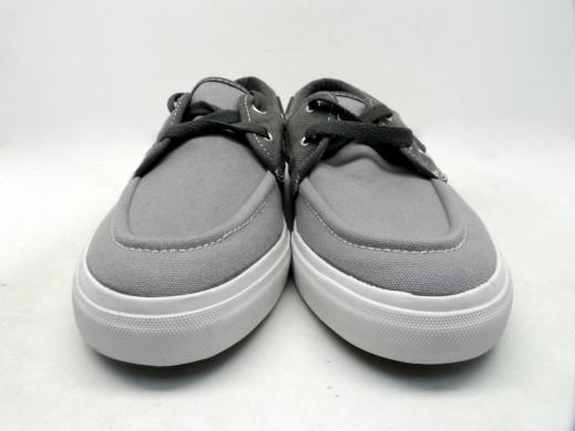 Egy pár fehér talpú szürke vászoncipő.