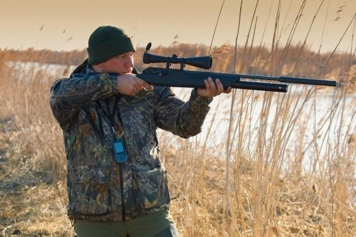 Egy vadász a nádasban puskáját célra tartja.
