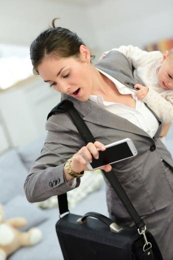 Egy nő, a hóna alatt kisbabájával, a másikban a telefonjával, a vállán laptoptáskával az óráját nézve rohan.