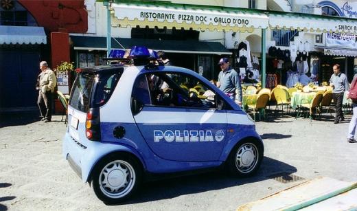 Egy kis kék POLIZIA feliratú autó áll az üzletek előtt.