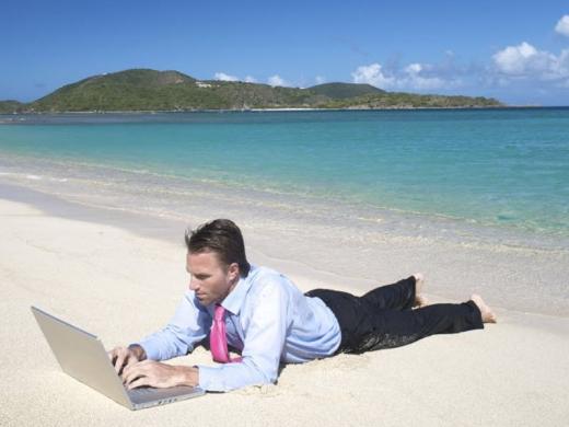 Egy nyakkendős férfi a tengerparton a laptopja előtt hasal és dolgozik.