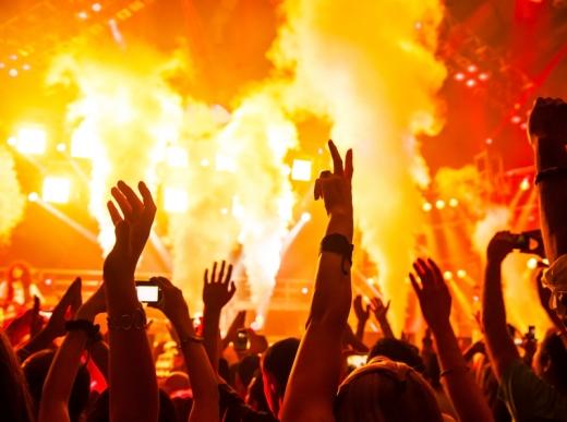 Egy színpad előtt csápoló fiatalok buliznak.