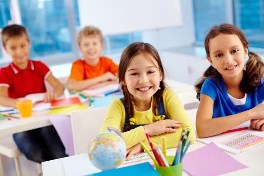 Az iskolapadban, elöl két lány, hátul két fiú ül és mosolyog.