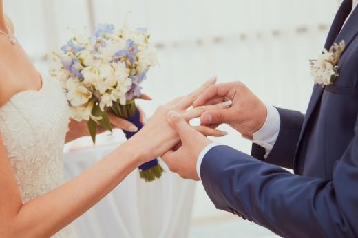 A vőlegény gyűrűt húz a menyasszony ujjra, akinek egy csokor van a kezében.