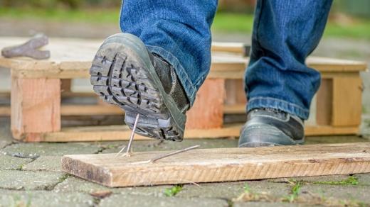A földön lévő deszkából kiálló szögbe lép egy munkás ember.