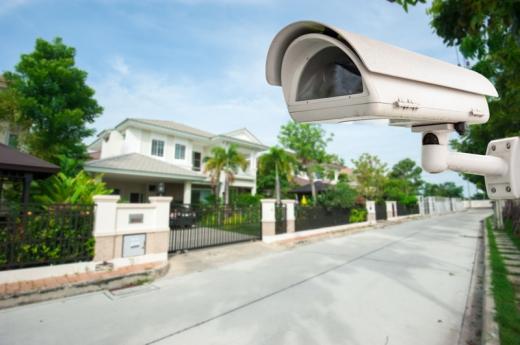 Egy kertvárosi utca, ahol az egyik kertkapunk van egy megfigyelő kamera.