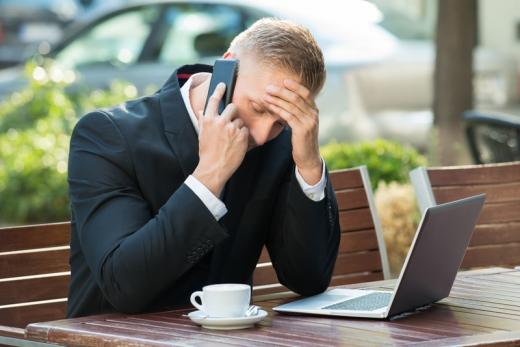 Egy férfi egy kávézó teraszán laptopja és kávéja előtt gondterhelten telefonál.