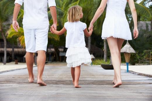 Egy fiatal pár, kislányukat közrefogva, kézen fogva sétál egy tengerparti fa hídon.