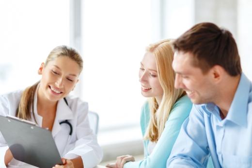 Egy doktornő egy képet mutat a mosolygós fiatal párnak.