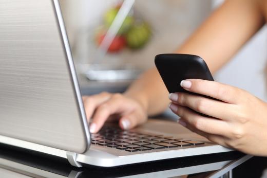 Egy nő kezei közül az egyik laptopon gépel, a másik telefont nyomkod.