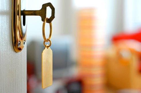Egy nyitott ajtó zárjában egy kulcs, amin lóg egy címke.
