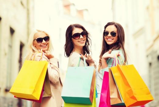 3 fiatal nő hátrafordulva mosolyog, bevásárlás után, szatyrokkal a kezükben.
