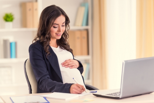Egy terhes nő ül az asztal és a laptop előtt, közben egy papírra ír valamit.