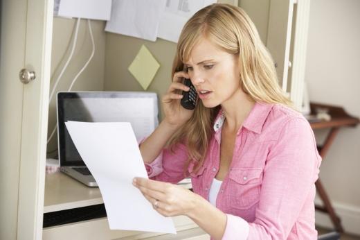 Egy nő felháborodottan telefonál, közben egy papírt tart a kezében.