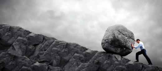 Egy férfi egy óriási követ tol fel egy dombon.