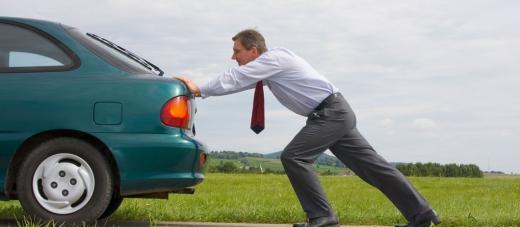 Egy férfi tolja a kék autóját.