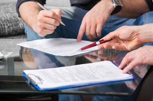 Az asztalon két szerződés: egyik férfi keze mutatja, hol kell aláírni a másik férfi keze pedig aláírja