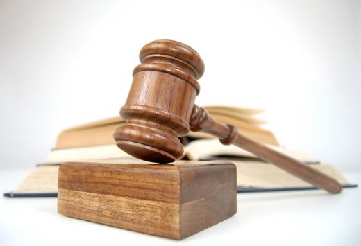 Egy bírói kalapács és törvénykönyvek vannak egy asztalon.