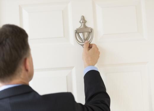 Egy férfi áll egy ajtó előtt, ahol épp a fém kopogtatóhoz nyúl.