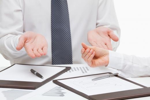 Az asztalon két mappa, egyik férfi széttárja a kezét, hogy nincs pénz, a másik pedig mutatja hogy kell a pénz.
