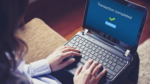 Egy nő gépel egy laptop előtt, amire az van írva, hogy Transaction completed.