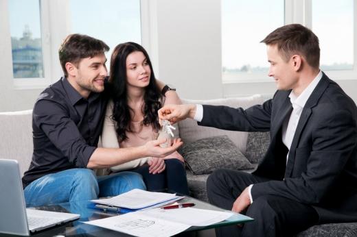 Egy fiatal pár kanapén ül és egy férfi a lakás kulcsait adja át neki.
