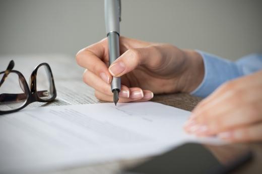 Egy kéz aláír egy szerződést az asztalon.