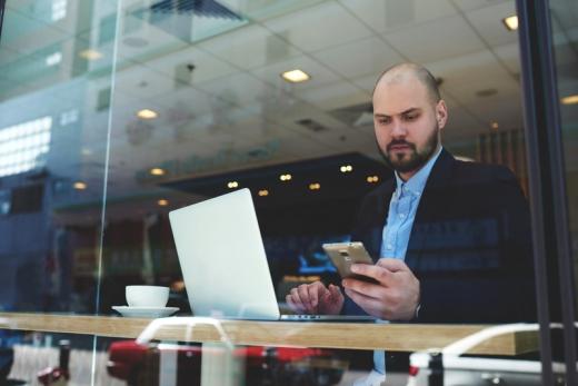 Egy férfi egy kávézóban laptop előtt telefont nyomkod.
