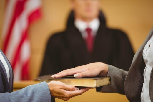 A bíró előtt egy nő a kezét a biblián tartva esküszik.