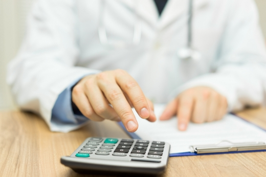 Egy orvos egyik keze számológépet használ a másik pedig egy papírra mutat.