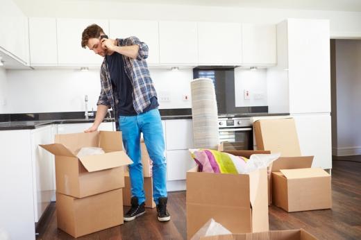 Egy férfi a konyhában dobozokba pakol és közben telefonál.