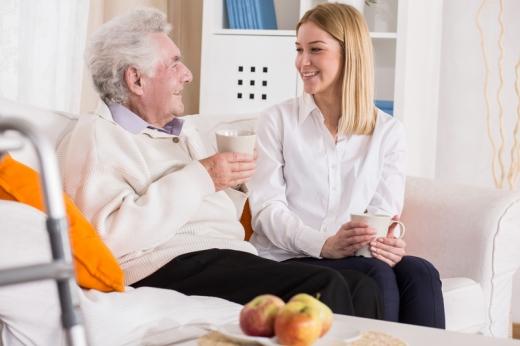 Egy öreg férfi és egy fiatal nő ül egy kanapénz és bögréből teát isznak.