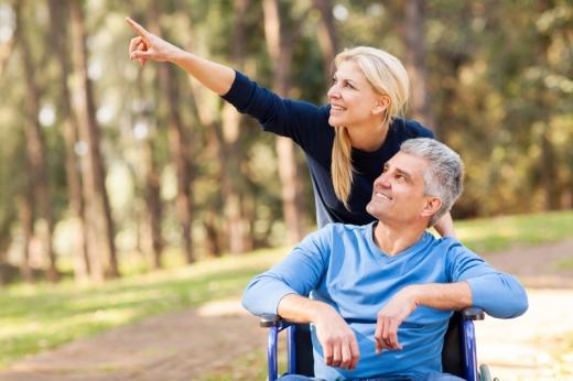 Egy középkorú férfi tolószékben ülve néz felfelé a fákkal övezett úton, feleséged pedig tolja és felfelé mutat.