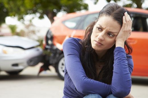 Egy nő fejét támasztja, mögötte karambolos autók.