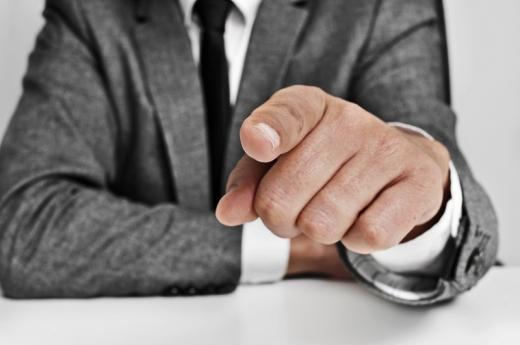 Egy férfi ül az asztalnál és egyik ujját kinyújtva felénk mutat.
