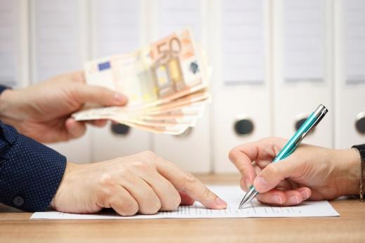 Az asztalon egy kéz aláír egy szerződést, egy másik pedig mutatja hol írja alá és pénzt ad.