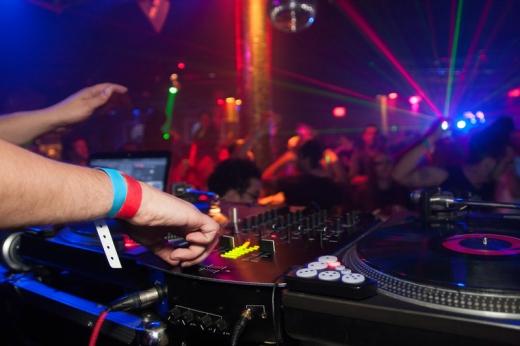 Egy diszkóban a dj éppen a hangerőt szabályozza, a tömeg pedig táncol.