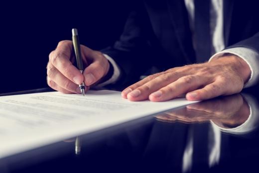 Az asztalon egy kéz aláír egy papírt.