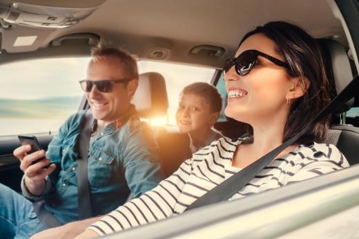 Egy vidám család az autóban: apuka telefont néz, anyuka vezet, kisfiú hátul mosolyog.