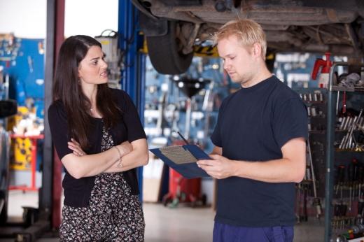 Egy szerelő egy mappát tart és a autó tulajdonos nőjének beszél.
