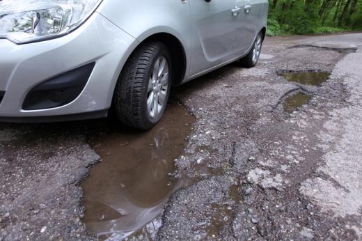 Egy autó első kereke bent áll egy vízzel teli kátyúban.