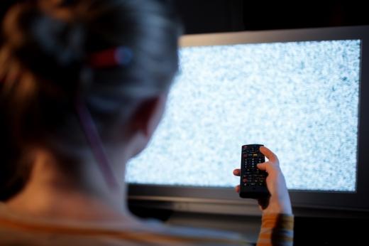 Egy nő háttal nekünk a távirányítót nyomkodja, de nincs kép a tévén.