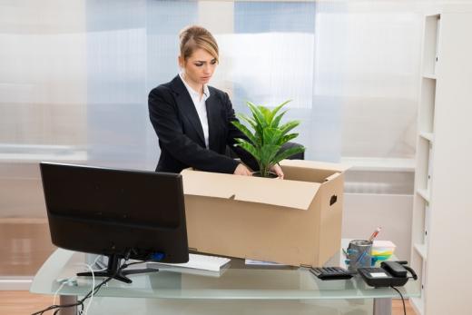 Egy nő kartondobozba pakolja a virágját az irodájában felmondás után.