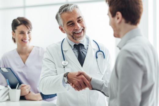 A beteg kezet fog az orvossal, asszisztens hátul mosolyog.