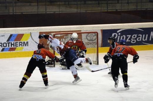 Két jégkorong védő ellöki a kapu felé támadó játékost.