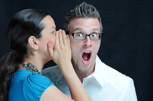 Egy nő kezét a szája elő tartva súg valamit egy meglepődött férfinek.